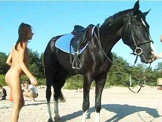 해변에서 말을 타지 않은 벗은 십대는 머리를 돌린다.