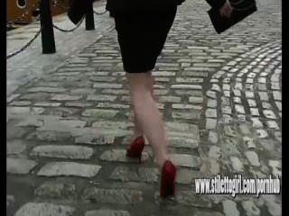 얇은 빨간색 stilettos 입고 자갈을 걷고 섹시한 높은 굽 여자