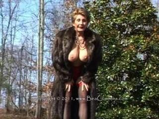 야외에서 자위하는 모피 코트에서 아가씨입니다.