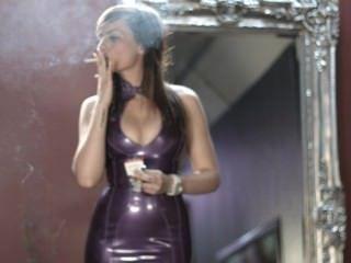 소녀는 자주색 라텍스 드레스에 강한 담배를 피우고