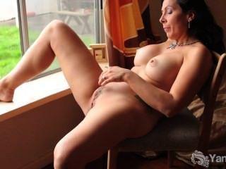 흥분한 창녀가 창문 앞에서 그녀의 음부를 문지른다.